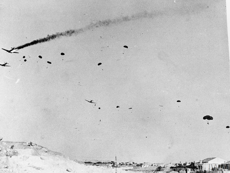 A blazing German troop-carrier (JU-52), hit by machine-gun fire from an entrenchment adjacent to the bombed area during the invasion of Crete, May 1941. Parachute troops and equipment are seen descending.