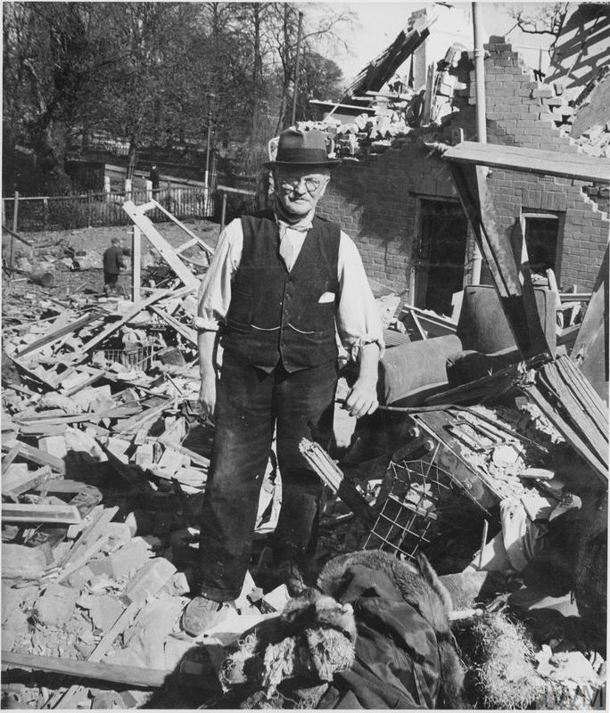 Mr McGregor stands amidst the debris of his house, following a Baedeker Raid on York. The Morrison shelter which saved his life, and the life of his wife and lodger is visible under rubble to the right of the photograph.