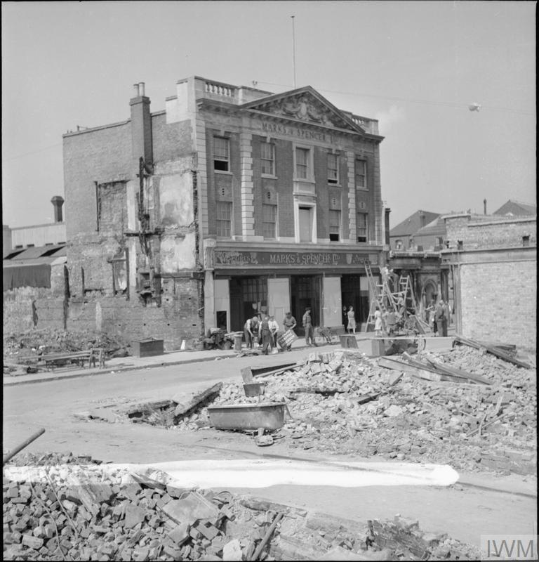 The windows of a Marks and Spencer store in Canterbury are boarded up following a devastating Baedeker raid on the Whitefriars area of Canterbury. In the foreground, piles of debris are all that is left of several buildings along the street. According to the original caption, a fire was started by incendiaries in the top of the Marks and Spencer building and was kept under control by Fire Guards until the National Fire Service arrived. A barrage balloon is just visible in the sky to the right of the photo.