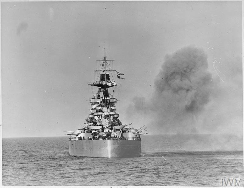 HMS RODNEY adds her weight of shells to the Navy's pounding of enemy positions along the Caen coast in support of the D-Day landings. Smoke is hanging over the starboard side (photograph taken from the frigate HMS HOLMES).