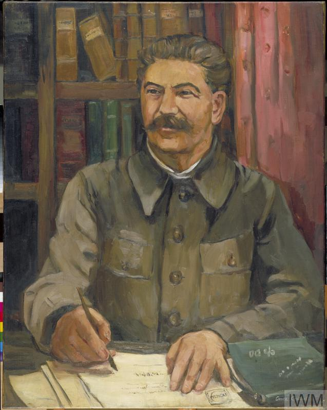 (© Art.IWM ARTLD 7213) A half-length portrait of Stalin sitting at a desk and signing papers. There is a bookcase behind him