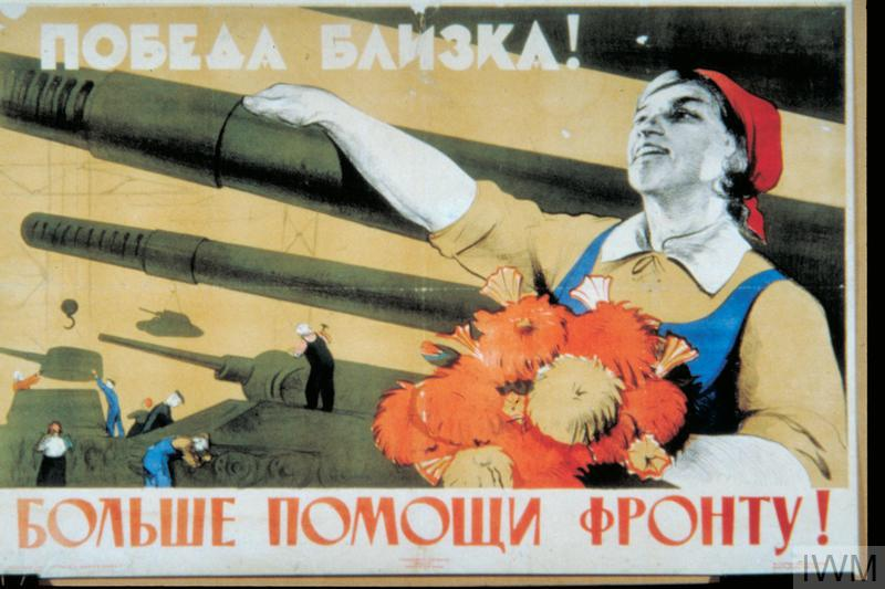 In the foreground a female tank worker holds a bouquet of flowers and rests her hand on the gun barrel of a completed Soviet T-34 tank. In the background workers construct two other T-34 tanks. text: [cyrillic Russian].