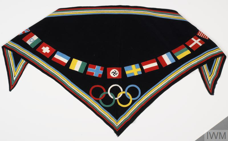 A predominantly black triangular scarf printed with flags of participant nations and Olympic rings.