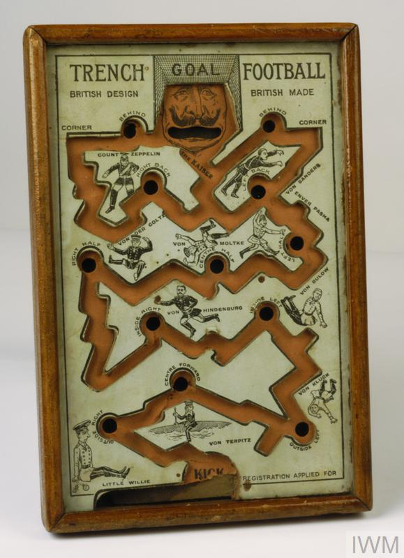 Trench Football dexterity game comprising rectangular box with wooden frame and glazed front, inside is a reconstruction of a twisting trench system with holes along the route through which a ball bearing must pass from the 'kick' spot at the base of the game box to the 'goal' being the Kaiser's mouth at the top, instructions for play are on the reverse.