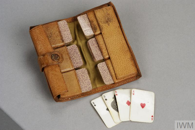Pocket playing card set consisting of: 1 small tan leather wallet secured with a press stud and containing six loops which hold the cards in place. 52 miniature playing cards that appear to be made from printed and laminated paper.