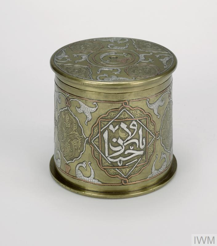 Ornate pot made from the lower part of a German cartridge (primer removed and hole filled). The lid for the pot is made from the same, and is detachable revealing the empty and cleaned interior. Both pot and lid have inlaid on the exterior three different coloured metals in patters which form stylised animals or birds and blocks of Arabic text.