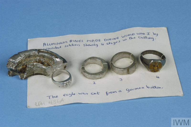 Set of four aluminum trench art rings, showing the various stages of development, from the fragment of German aluminum nose cone through to completed ring decorated with eagle from German button.