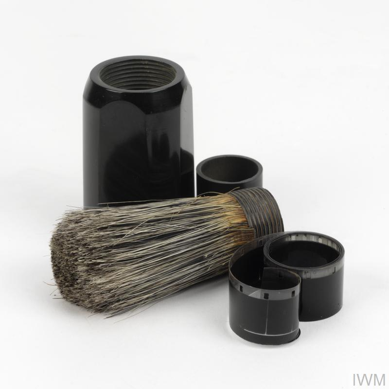 © IWM (EPH 10068) A standard male shaving brush with black, plastic handle and wooden base. One reel of miniature film can be contained within the 'hollowed-out' handle of the brush.