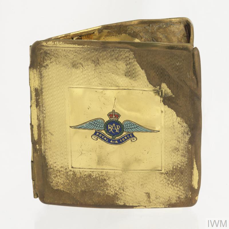 Tarnished gold painted metal cigarette case with RAF badge transfer on top of lid, the cigarette case is mis-shapen and will not shut, the outside of the case is engraved with a shallow zig-zag style geometric pattern, the inside of the case is undecorated and there is a retaining elastic band to keep cigarettes secure to one side.