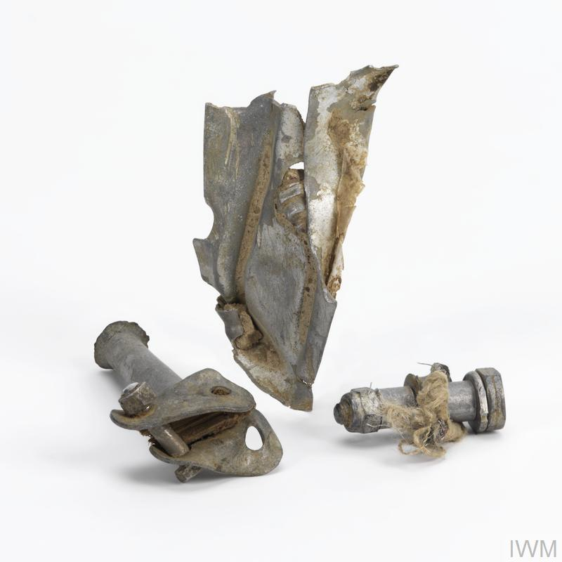Three aircraft fragments, the first being a metal bolt with twisted wire attached, the second being part of a supporting bracket - tubular in shape with flattened brackets at one end which are each machined with a pair of holes, and the third being a twisted fragment of aluminium showing a partial stamp reading '25 C'.