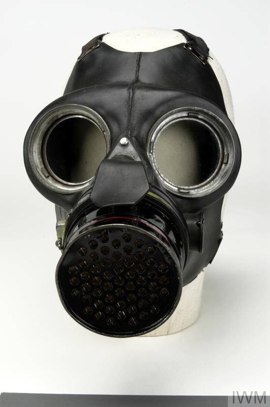 Respirator with canister: black leather mask with round glass eyepieces in metal surrounds; rubber exhale valve flap protrudes from font of nose; front of mask is open, with cylindrical canister inserted into opening and sealed with metal clip ring; cylinder is painted black with thin green and red stripes around it, towards the front; black elastic harness.