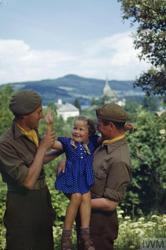 Two soldiers of the Royal Military Police in the Klagenfurt area with Anna, a 4 year old Austrian girl with whose family the men were billeted.