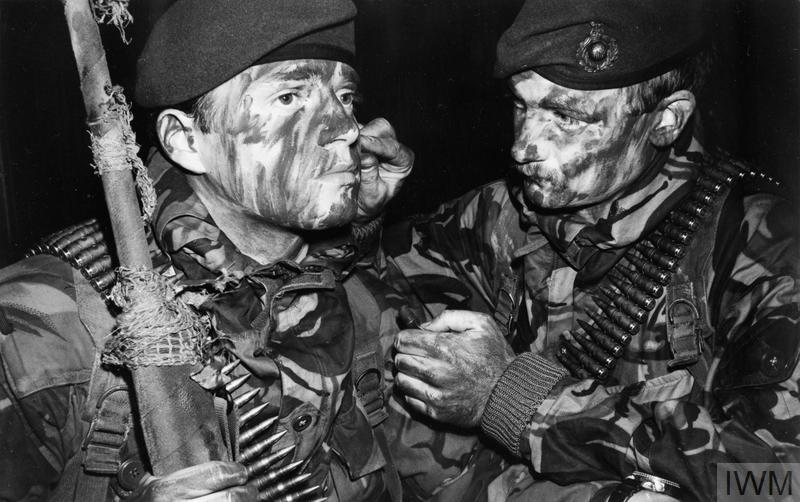 A Royal Marine of 3 Commando Brigade helps another to apply camouflage face paint in preparation for the San Carlos landings on 21 May 1982.