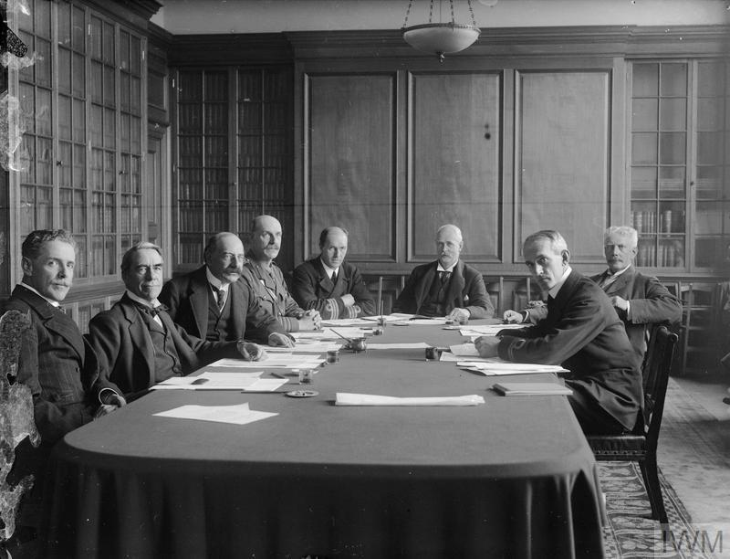 The Chairman and Committee of the Imperial War Museum seated around a table. Left to right: Ian Malcolm (Art), Martin Conway (Director General), Alfred Mond (Chairman), Colonel J.R. Stansfield (Munitions), Captain C.C. Walcott (Admiralty), B.B. Cubitt (War Office), C.W.C. Oman (Library) and Lieutenant Charles ffoulkes (Secretary). Late September/early October, 1917.