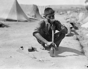 The carpenter of an Indian transport camp smokes a home-made pipe, constructed from a pickle jar, a tin funnel and two hollow canes. He is crouching on the ground and wears sunglasses. THE INDIAN ARMY IN SALONIKA DURING THE FIRST WORLD WAR