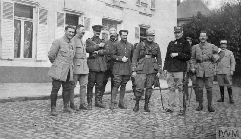 Major Winston Churchill, wearing a French steel shrapnel helmet, stands with General Emile Fayolle and other officers including Captain Edward Spears (third from left) at the headquarters of XXXIII Corps, French Army, at Camblain L'Abbe while visiting the French front line on 15 December 1915.