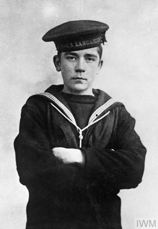 A half length portrait widely attributed as being Boy (1st Class) John 'Jack' Travers Cornwell, though current research suggests it is likely to be one of his brothers. Cornwell was posthumously awarded the Victoria Cross for remaining at his post at the forward 5.5 inch gun of the cruiser HMS CHESTER. The ship was badly shelled by four German cruisers and Cornwell's position was hit four times, killing all the crew apart from Cornwell.