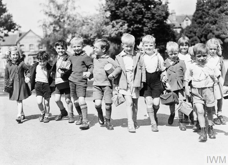 A group of smiling evacuees with gas mask boxes hold hands on a walk in Reading.