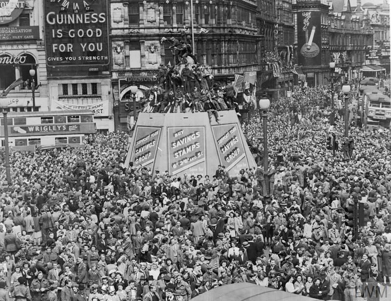 A mass of civilians and servicemen crowding around Piccadilly Circus, London.