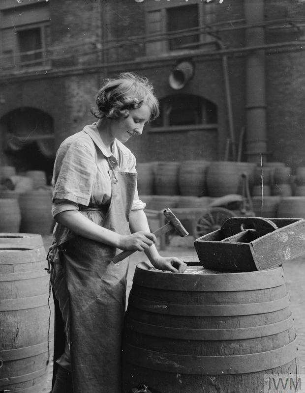 A portrait of a female brewer, as she use a hammer and nails to secure the lid of a cask or barrel at a brewery in London.