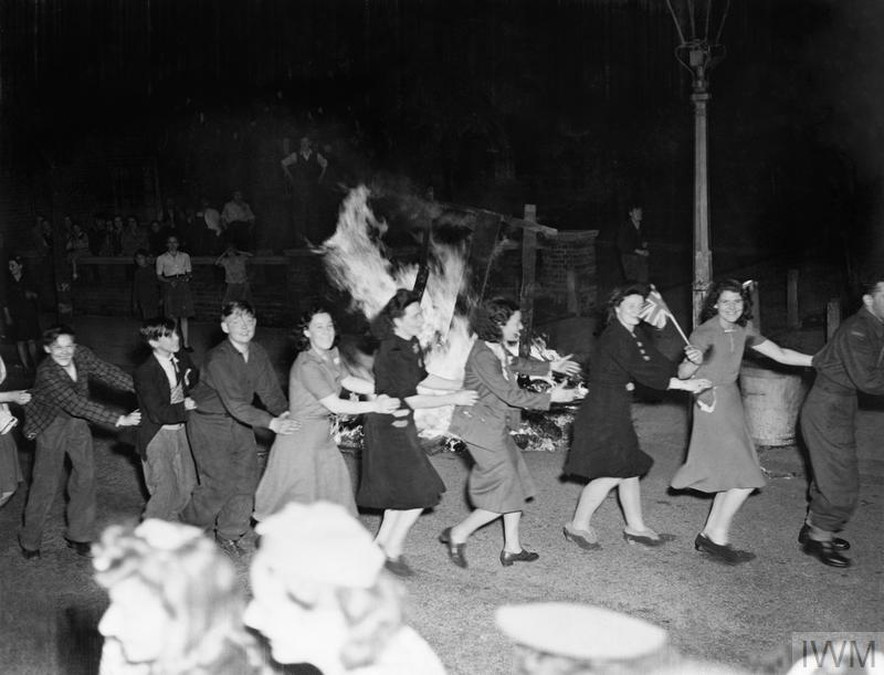 Men and women dance the conga around a bonfire in East Acton, London during the evening of VE Day, 8 May 1945.