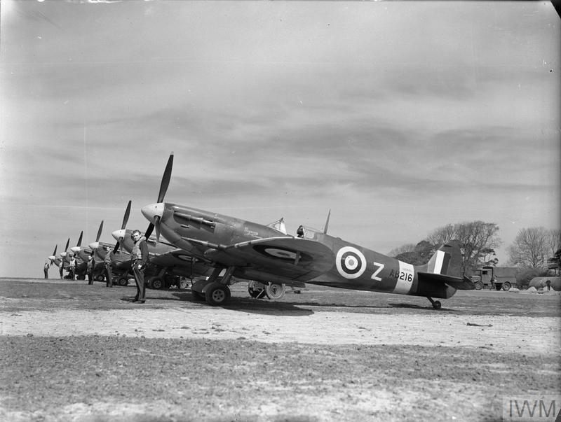 Spitfire Mk Vs of No. 91 Squadron lined up at Hawkinge, May 1942. Standing nearest the camera is the Squadron's Commanding Officer, Squadron Leader R W Oxspring, in front of his personal aircraft, a Mark VC, AB216: DL-Z. Next to him, in front of another Mark VC, is the 'B' Flight commander, Flight-Lieutenant F H Silk. The remaining aircraft are Mark VBs.