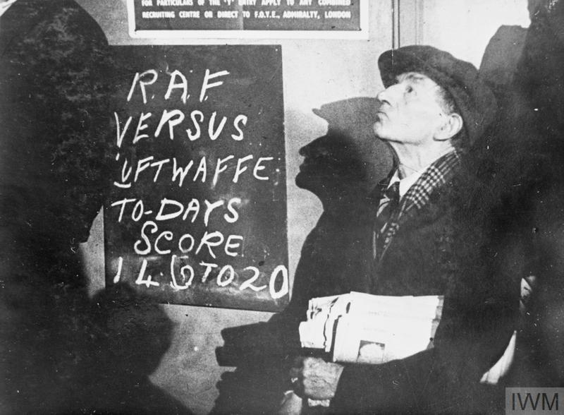 "A newspaper seller in the street watching a ""dog-fight"" during the Battle of Britain."