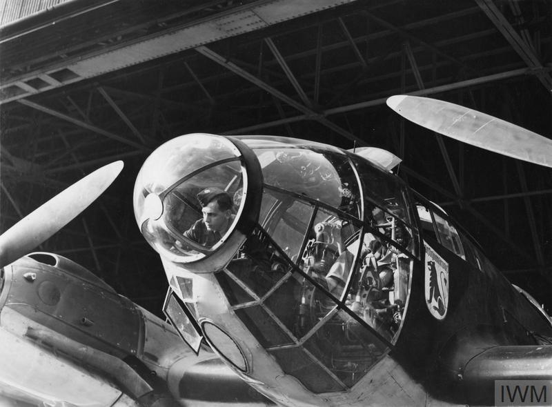 An RAF airman examines the cockpit of a captured German Heinkel He 111.