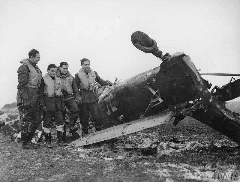 Spitfire pilots pose beside the wreckage of a Junkers Ju 87 Stuka, which they shot down near Manston Airfield, 5 February 1941. Airmen , L-R are Pilot Officer C.H. 'Sammy' Saunders, Sgt R. 'Titch' Havercroft, Sgt Hugh Bowen-Morris & Pilot Officer Ronald Fokes.