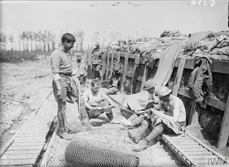 Troops of the 2nd Australian Division in a support line trench; Armentieres, May 1916. Two men on right appear to be 'chatting' i.e. searching their shirts for lice.