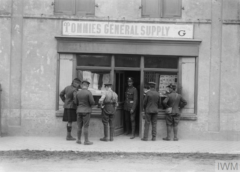 """Shop in the village of Ghyvelde near Dunkerque, 6th August 1917. Note the sign """"Tommies General Supply"""", Branch G."""