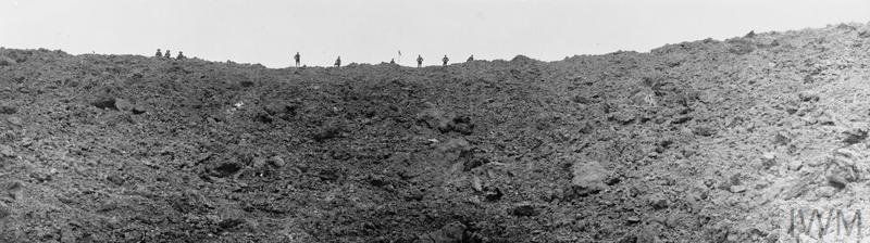 British soldiers stand looking into the huge mine crater at Messines Ridge, blown up on the morning of the battle. Photographed on 11 June 1917