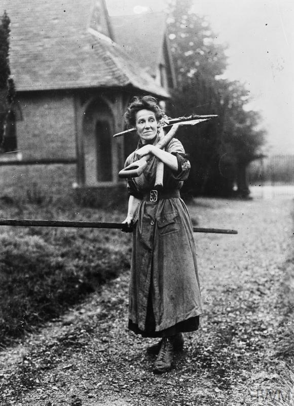 Mrs Kitchener, A female gravedigger, stands on the church path with her spade and pick over her shoulder