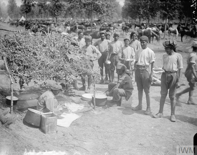 A group of Indian soldiers, possibly soldiers of the 9th Hodson's Horse (wearing just shirts and trousers), stand round the improvised cookhouse at an Indian cavalry camp near Querrieu whilst two seated cooks prepare some food. Indian Cavalry Camp. 29 July 1916.