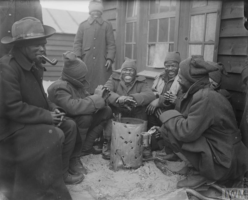 Troops of the South African Native Labour Corps around a brazier at their camp. Dannes, March 1917.