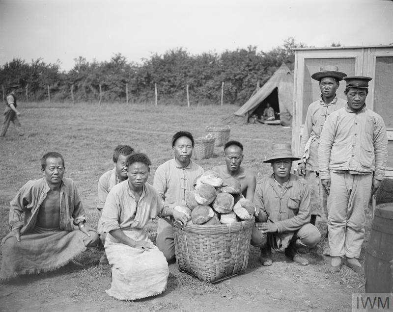 Men of the Chinese Labour Corps in their camp at Caestre with loaves of special bread made in their own bakeries