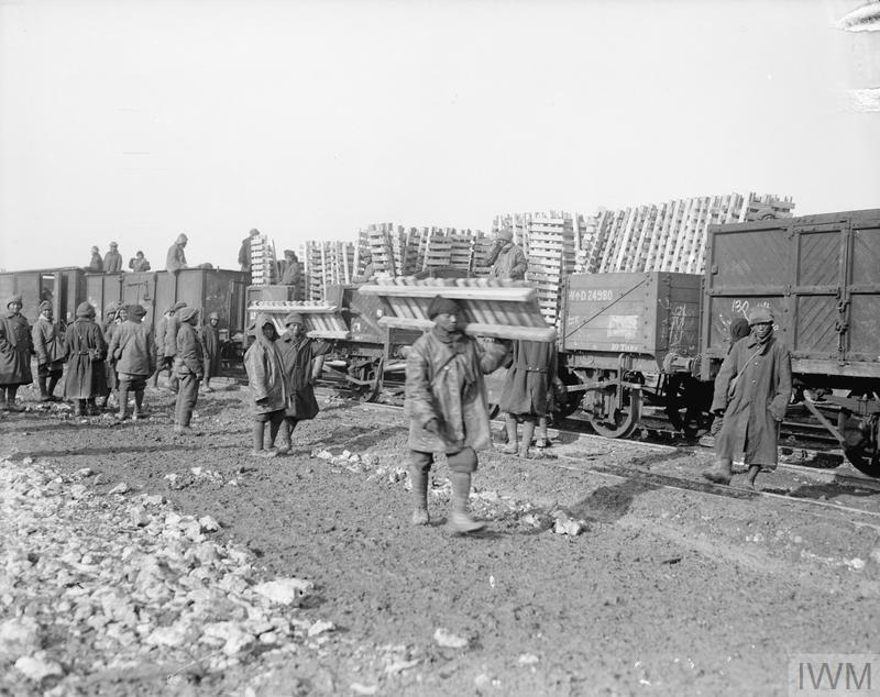 Men of the Chinese Labour Corps unloading duck boards at a railway siding at Ytres, 2 February 1918.