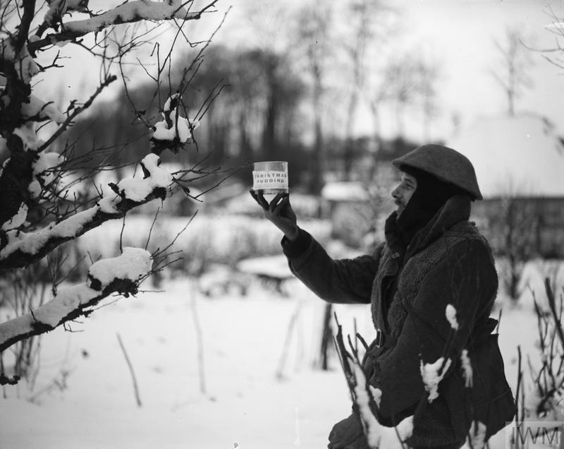 British soldier displaying a can of Christmas pudding at snow-covered Neulette, 17 December 1917.