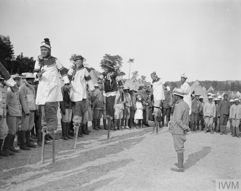 Chinese stilt-walkers entertaining an audience of British and American soldiers, local inhabitants and Chinese workers, 26 May 1918