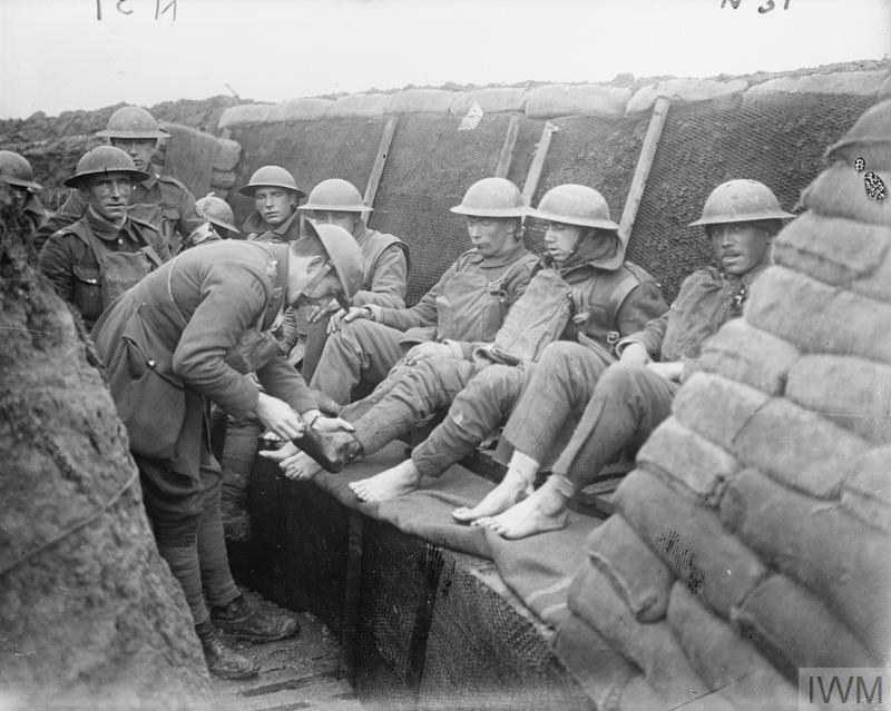 The Medical Officer of the 12th Battalion ,East Yorkshire Regiment conducts a foot inspection in a support trench near Roclincourt, 9 January 1918.