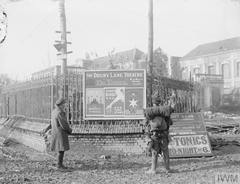 British soldiers looking at theatre posters in Bapaume advertising 'The Tonics' concert party, 30 January 1918.
