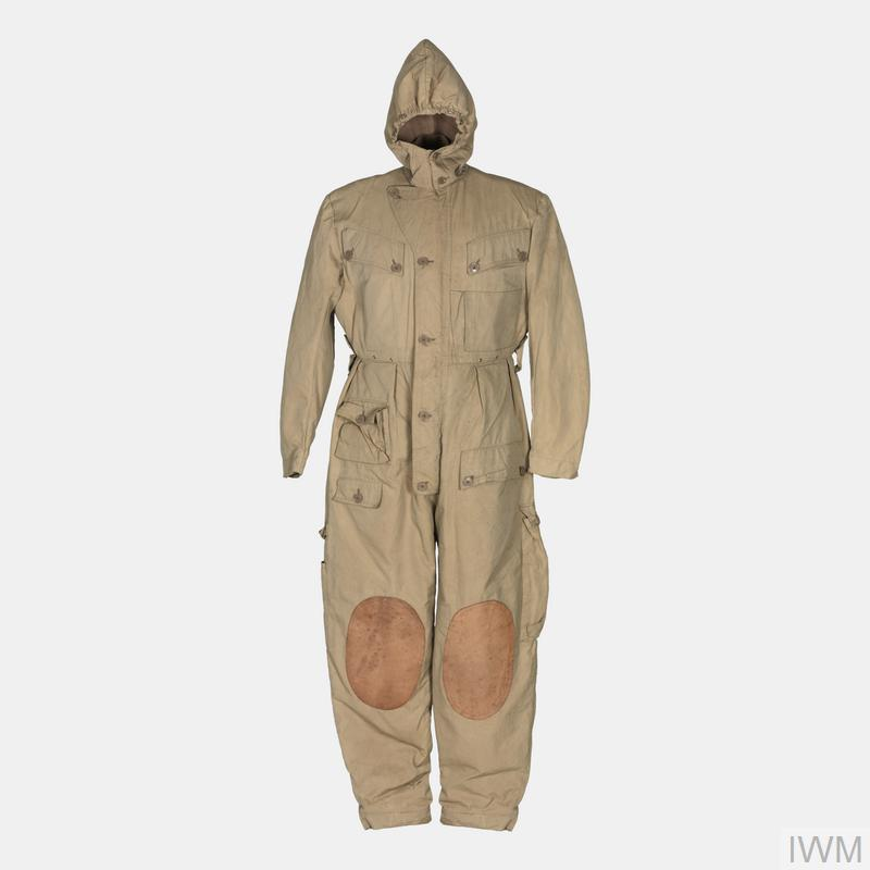 One-piece overalls-styled oversuit with fitted hood with external pockets, of light khaki fabric.