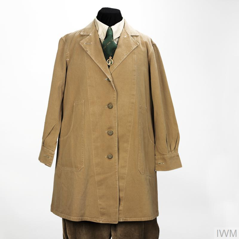 coat Light brown 3/4 length single-breasted open-collared overall coat made of drill material. Fitted to each hip are deep flapless pockets and a cloth belt is attached to the rear of the garment. Fitted to the front are four olive-coloured plastic detachable buttons, secured to the coat by removable shanks, as are the single buttons attached to the cuffs.