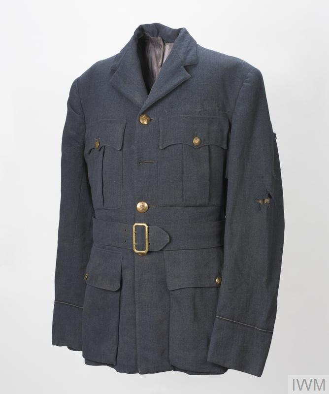 Single-breasted open-collared four-pocket jacket of RAF blue. The cuffs feature single rank braid rings (Pilot Officer) and all but one of the RAF officer quality crested buttons are present (one re-sewn by curator back in position (top) as it became detached during examination, 4/Dec/2009). The integral cloth belt fitted with brass open double-claw buckle it attached.