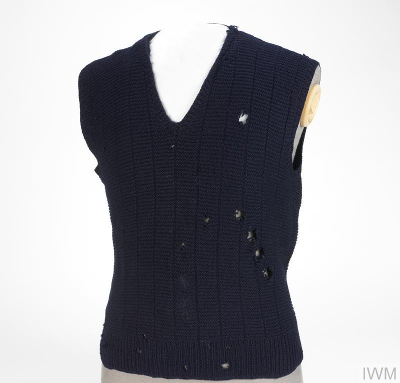 © IWM (UNI 127805) Woolen jumper with darned bullet hole.