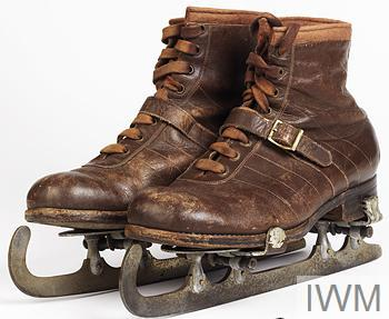 A pair of brown leather boots with brown laces and a brown leather strap across the laces. A pair of metal clip-on ice skates are attached (by screws at the base) to the undersides of the boots.
