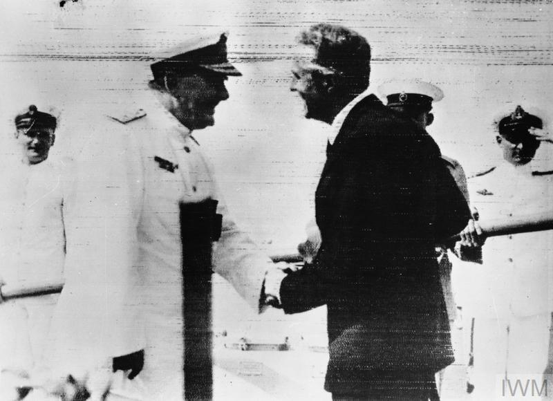 Rear Admiral Sir Henry Harwood is greeted by the British Minister to Uruguay, Mr E Millington-Drake after his arrival at Montevideo. Admiral Harwood arrived in the cruiser HMS AJAX after the battle of the River Plate and the scuttling of the ADMIRAL GRAF SPEE.