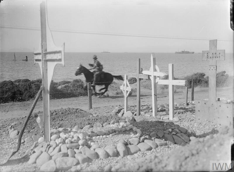 An Australian despatch rider galloping along the coast road at Anzac Cove to avoid sniping. He is passing a war cemetery. Out to sea is a hospital hip and a cruiser.