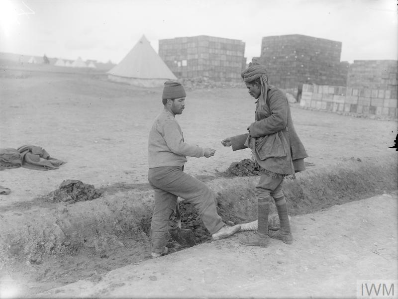 An Indian soldier exchanging coins with a man of the Greek Labour Corps at Salonika.