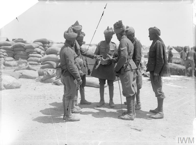 """Troops of the 14th Sikhs of the 29th Indian Infantry Brigade examining a piece of shell from """"Asiatic Annie"""" that fell in their camp."""